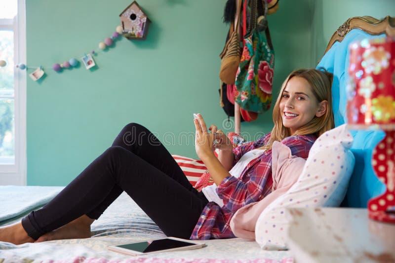 Vrouw die op Bed liggen die thuis Mobiele Telefoon met behulp van royalty-vrije stock afbeeldingen