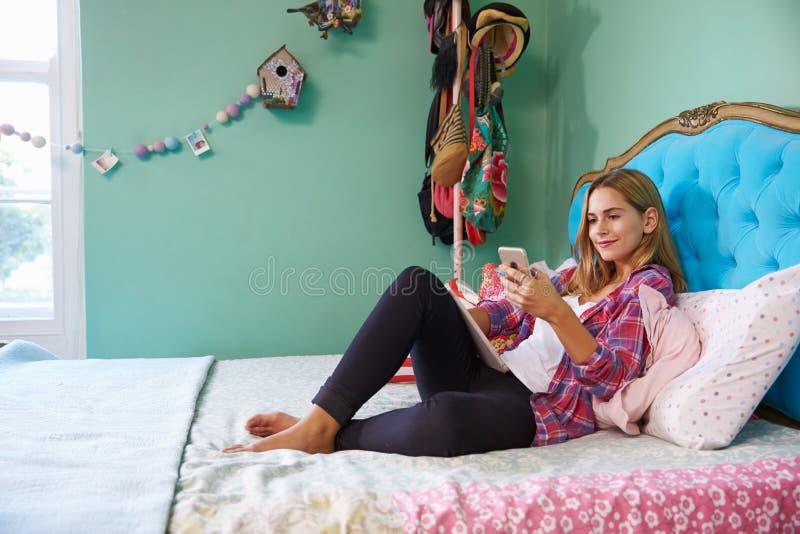 Vrouw die op Bed liggen die thuis Mobiele Telefoon met behulp van royalty-vrije stock foto's
