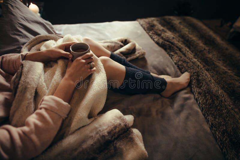 Vrouw die op bed met een kop van koffie liggen stock foto