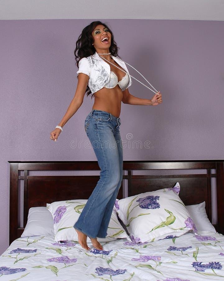 Vrouw die op bed springt royalty-vrije stock afbeeldingen