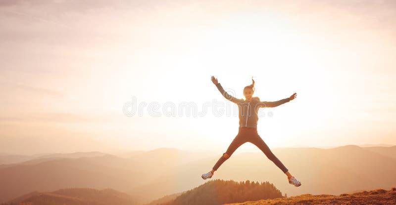 Vrouw die op berg op zonsonderganghemel en bergenachtergrond springen royalty-vrije stock foto's