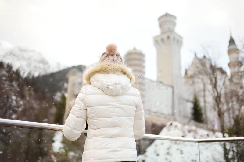 Vrouw die op beroemd koninklijk kasteel Neuschwanstein in de winterdag kijken royalty-vrije stock foto