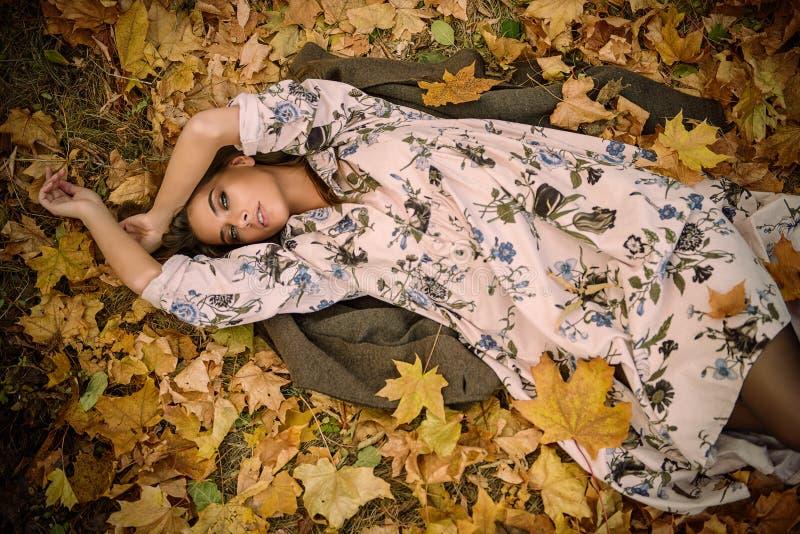 Vrouw die op bladeren ligt stock afbeeldingen