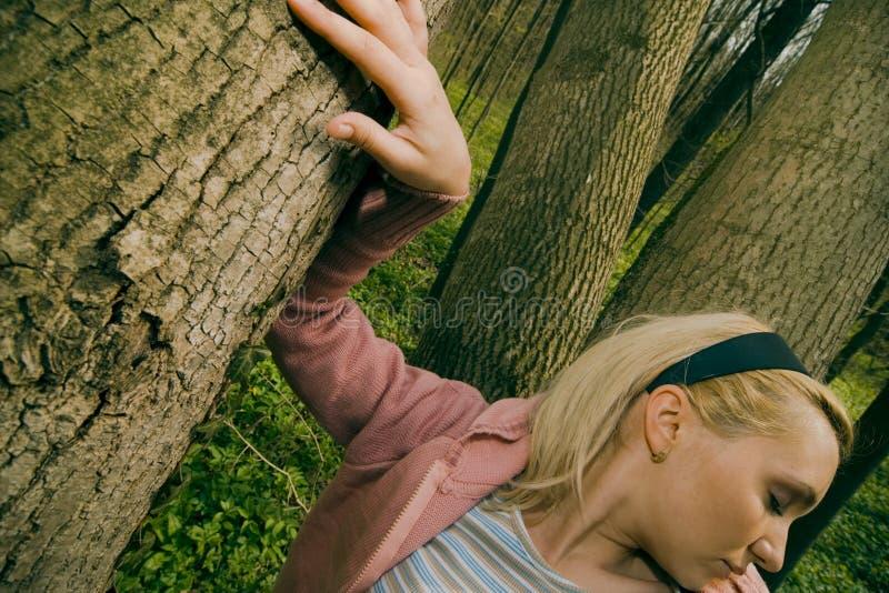 Vrouw die op boomboomstam leunt. stock foto's