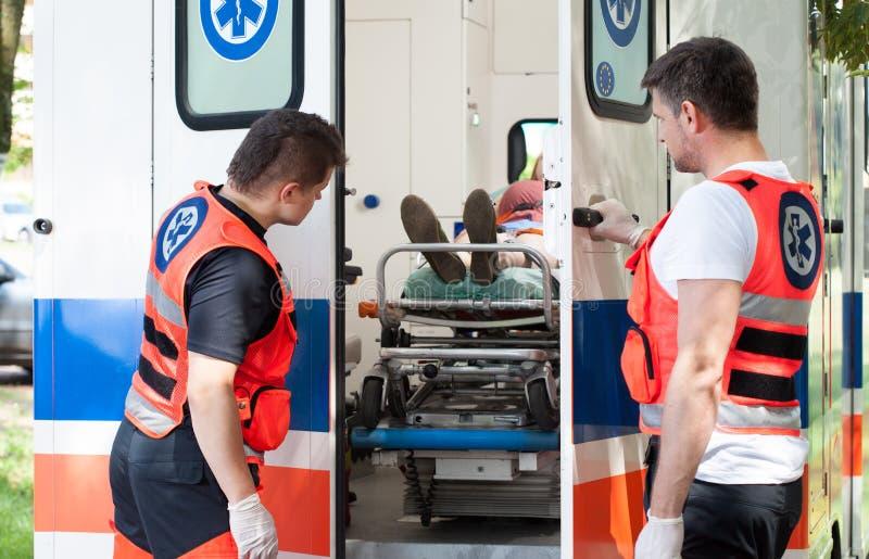 Vrouw die op brancard in ziekenwagen liggen stock afbeelding