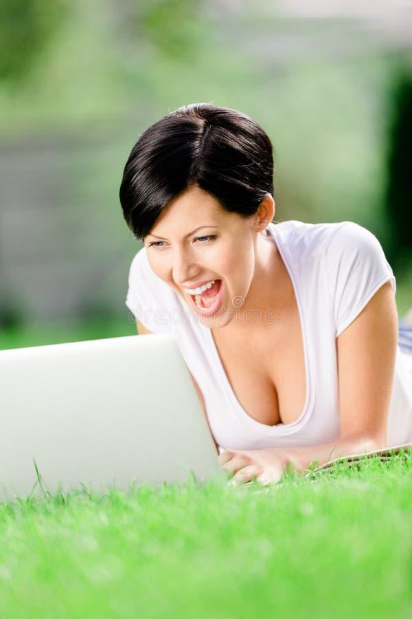 Vrouw die op de graswerken bij laptop liggen stock fotografie