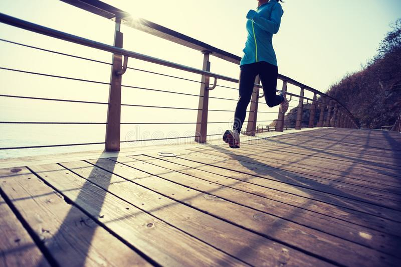 vrouw die op de houten kust van de promenadezonsopgang lopen stock fotografie