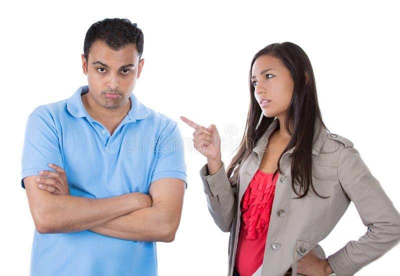 Vrouw die op de mens richten alsof slechte jongen te zeggen omdat hij verkeerd iets deed stock foto's