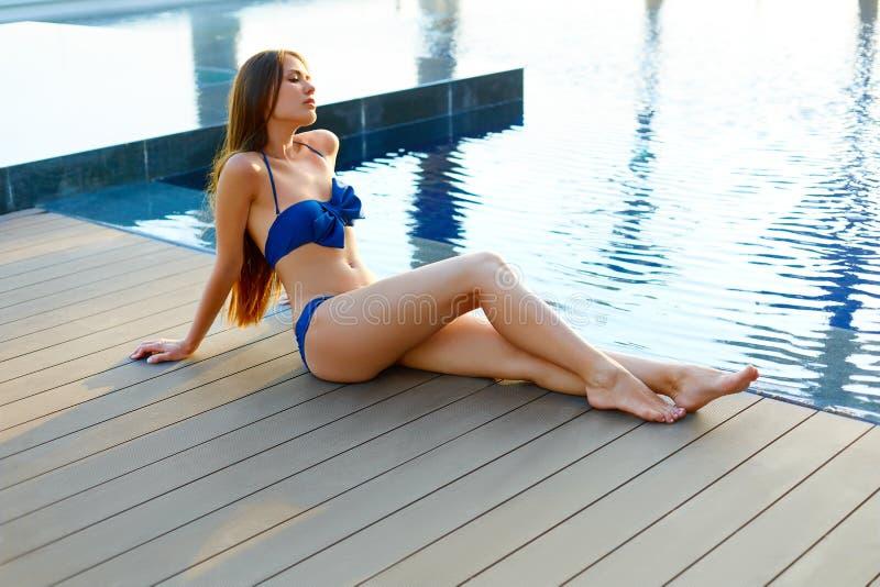 Vrouw die op de richel van de pool zonnebaden stock afbeeldingen