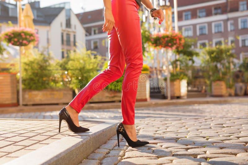 Vrouw die op de straat in rode broeken lopen stock fotografie