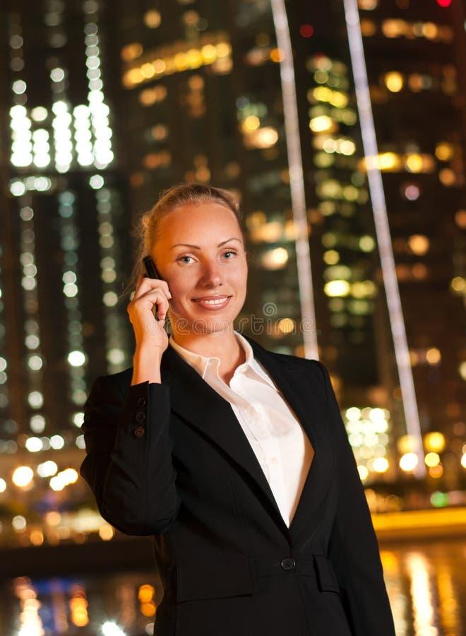 Vrouw die op de telefoon in de grote stad spreekt royalty-vrije stock afbeeldingen