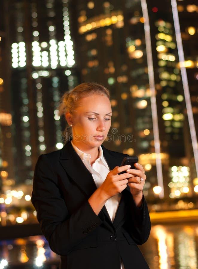 Vrouw die op de telefoon in de grote stad spreekt stock afbeelding