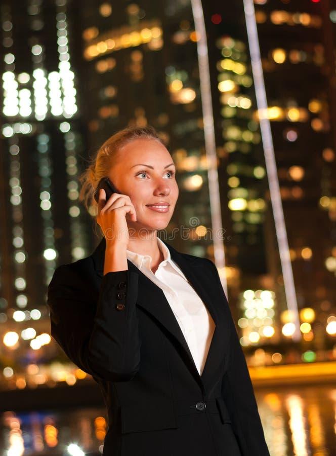 Vrouw die op de telefoon in de grote stad spreekt royalty-vrije stock foto's
