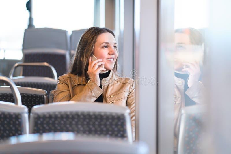 Vrouw die op de telefoon spreken terwijl het berijden van de bus, de trein of metro stock afbeeldingen