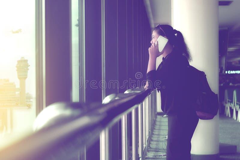 Vrouw die op de telefoon spreken terwijl het wachten op haar vlucht royalty-vrije stock afbeelding
