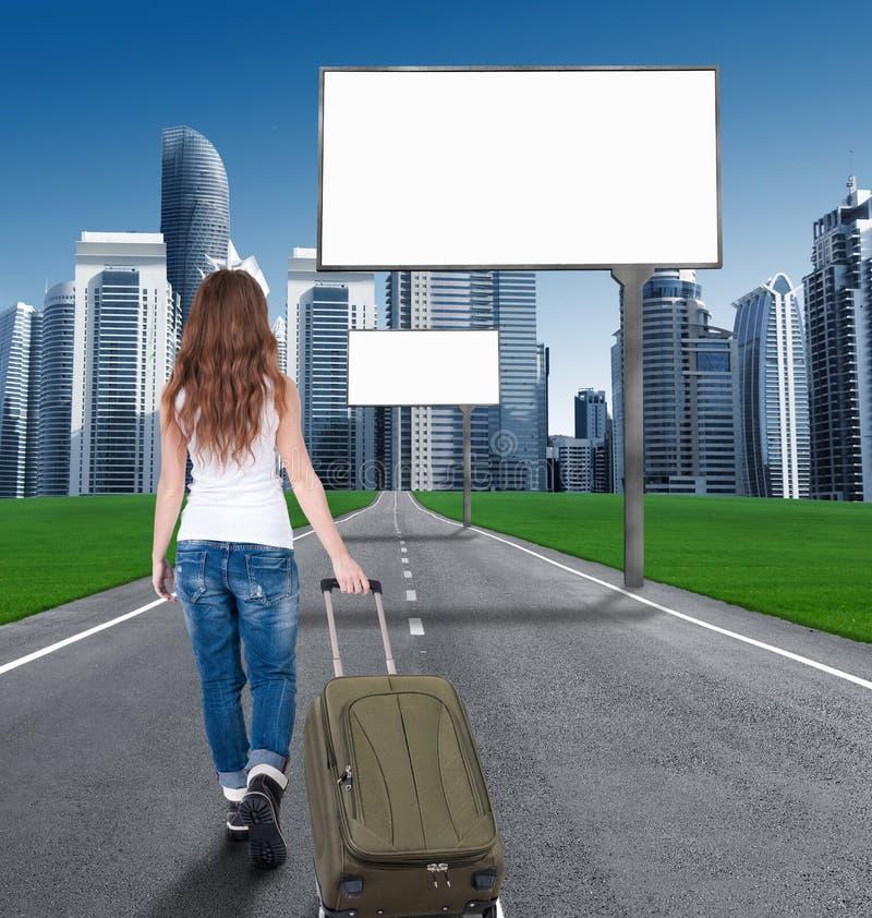 Vrouw die op de weg aan de stad lopen stock fotografie