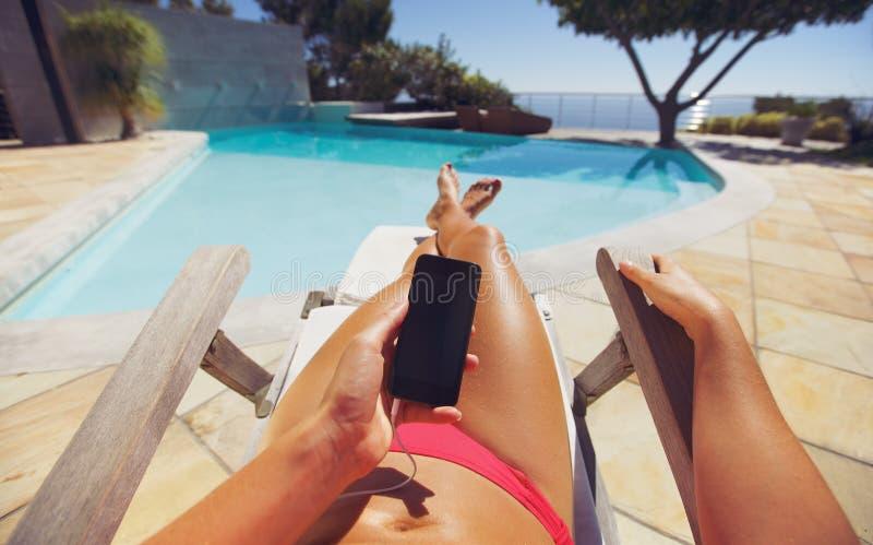 Vrouw die op deckchair met telefoon zonnebaden stock afbeelding