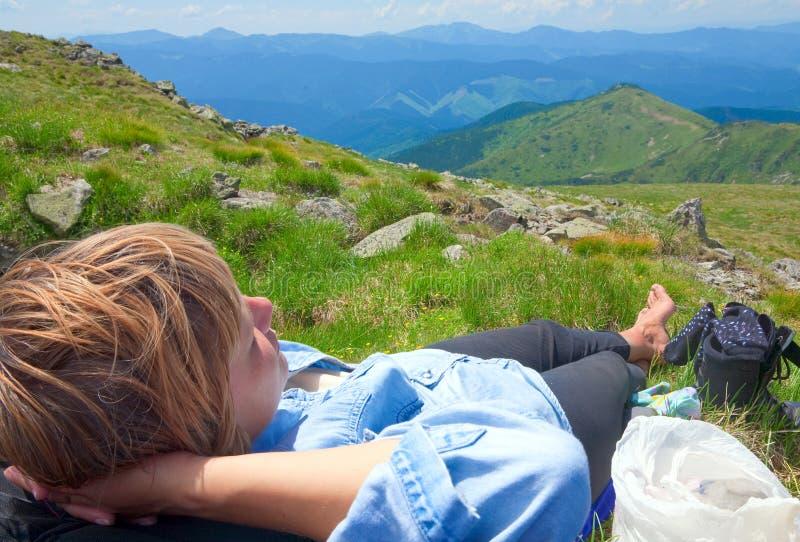 Vrouw die op een bergbovenkant rust stock fotografie
