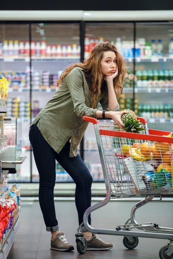 Vrouw die op een boodschappenwagentje bij de supermarkt leunen royalty-vrije stock foto