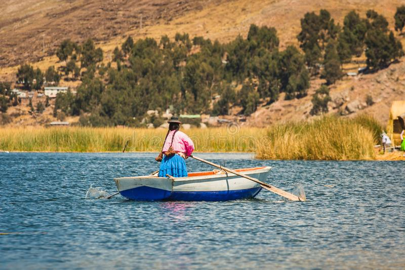 Vrouw die op een boot, Uros-eiland, Titicaca-Meer, Peru roeien royalty-vrije stock afbeeldingen
