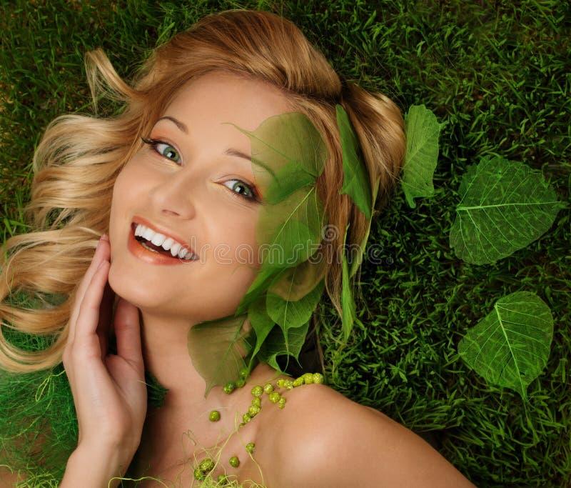 Vrouw die op een de lentegras liggen royalty-vrije stock foto