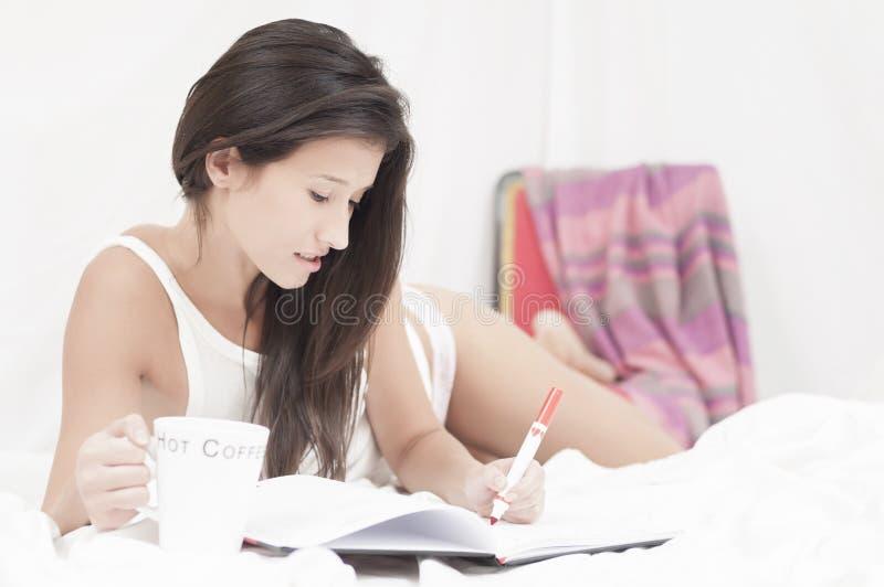 Vrouw die op een een notitieboekje en het drinken koffie schrijft stock foto's