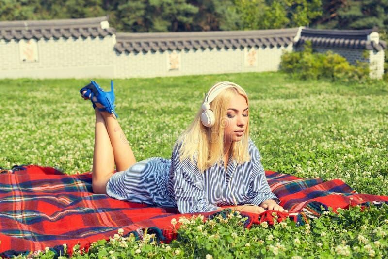 Vrouw die op een groene weide liggen en aan muziek luisteren royalty-vrije stock fotografie