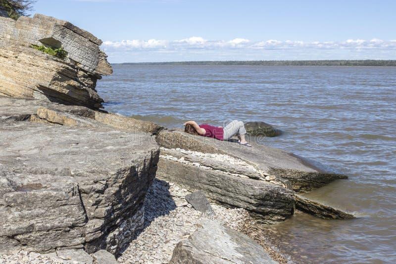 Vrouw die op een groot keirecht liggen naast het meer die van de zon genieten stock afbeelding