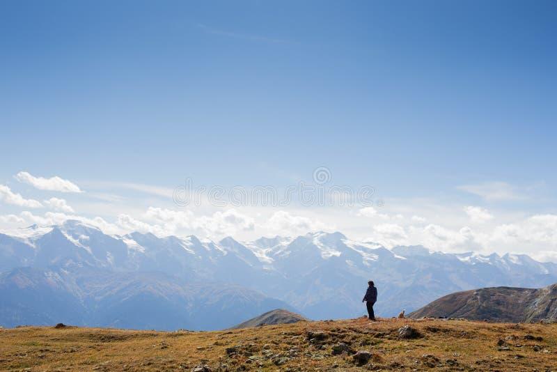 Vrouw die op een klippenrand hoog opstaan in de bergen stock afbeelding