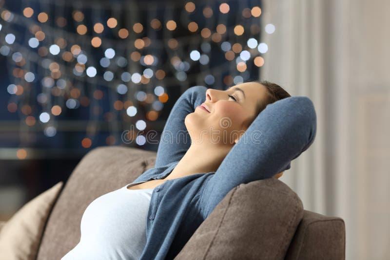 Vrouw die op een laag in de nacht thuis rusten stock foto