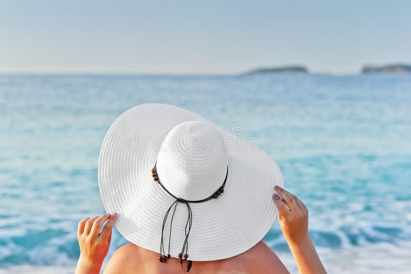 Vrouw die op een ligstoel op het strand zonnebaden en handenhoed houden stock afbeeldingen