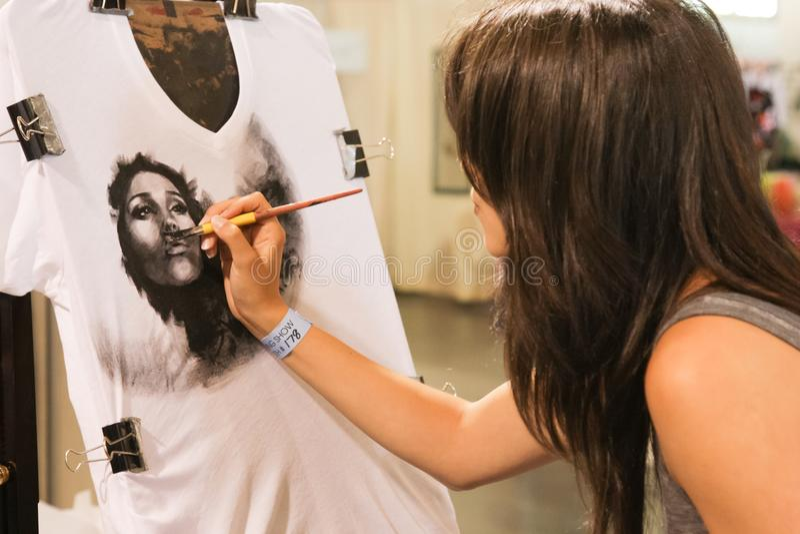 Vrouw die op een overhemd trekken stock foto