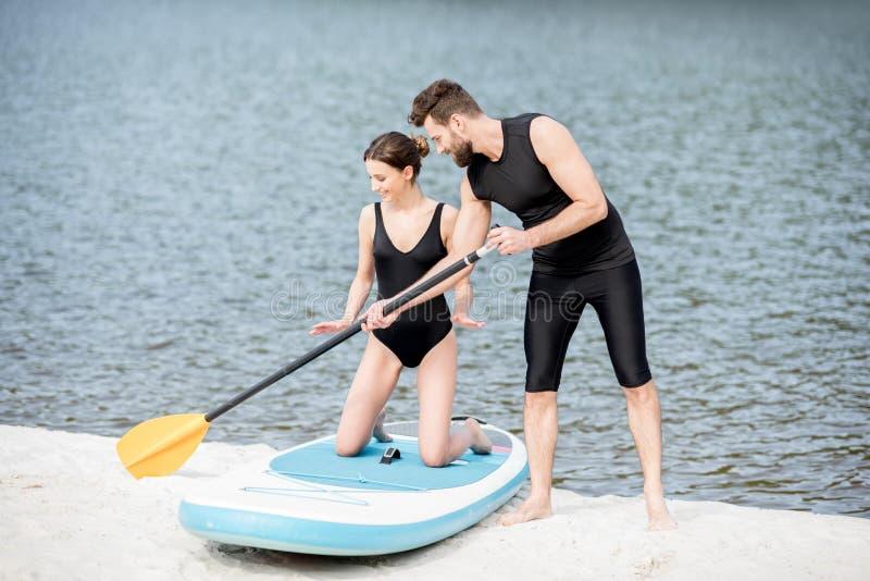 Vrouw die op een paddleboard met instructeur leren te surfen stock foto