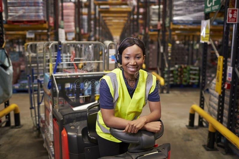 Vrouw die op een slepentractor leunen in een distributiepakhuis stock foto