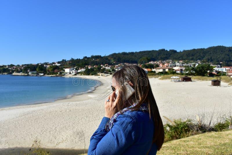 Vrouw die op een smartphone in een strand spreken Strand met helder zand en turkoois water Klein kustdorp met promenade en voor stock afbeelding