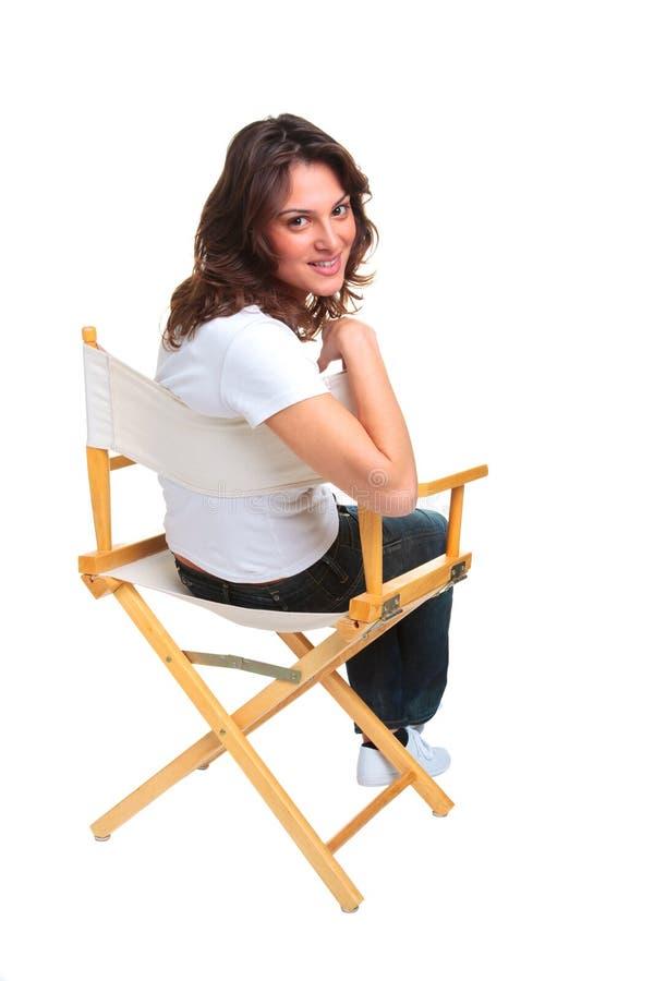 Vrouw die op een stoel wordt gezeten die terug eruit ziet stock foto's