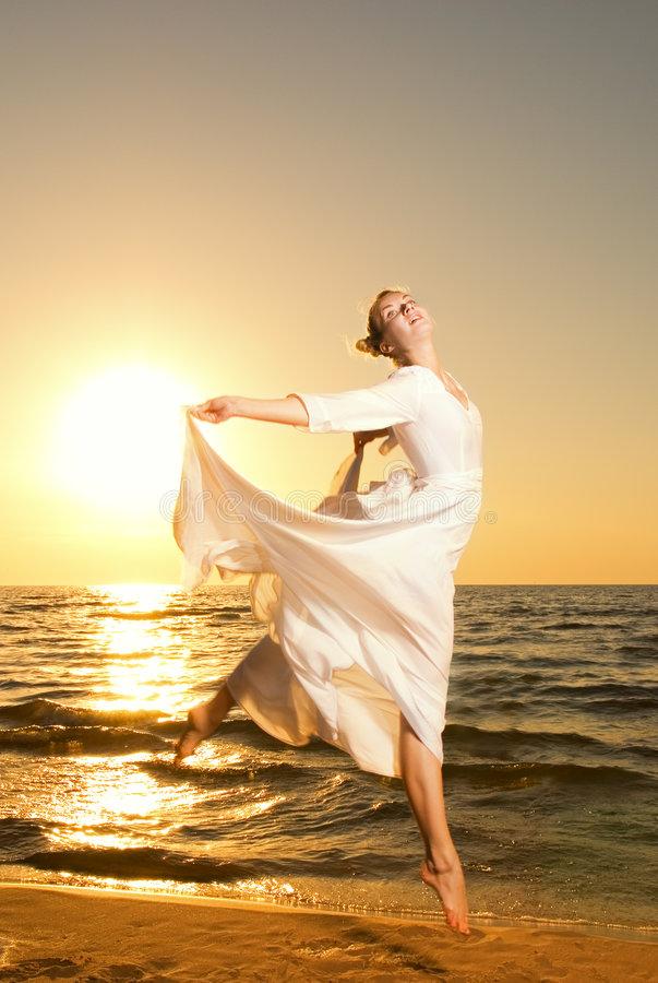 Vrouw die op een strand springt stock afbeeldingen
