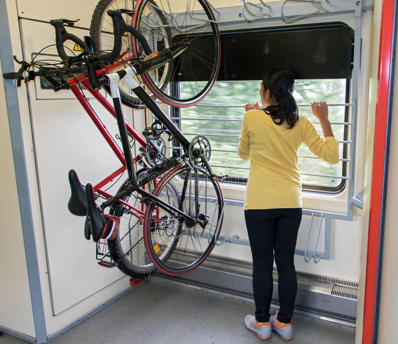 Vrouw die op een trein met een fiets reizen stock afbeelding