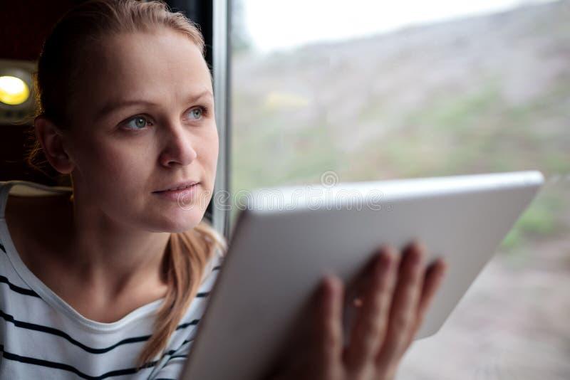 Vrouw die op een trein met een tablet reizen royalty-vrije stock foto's