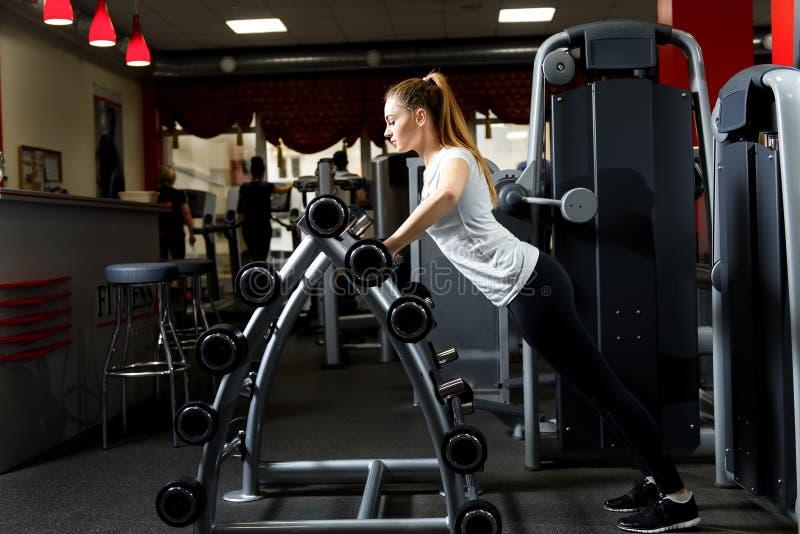 Vrouw die op een tribune van barbells in een gymnastiek leunen stock foto's
