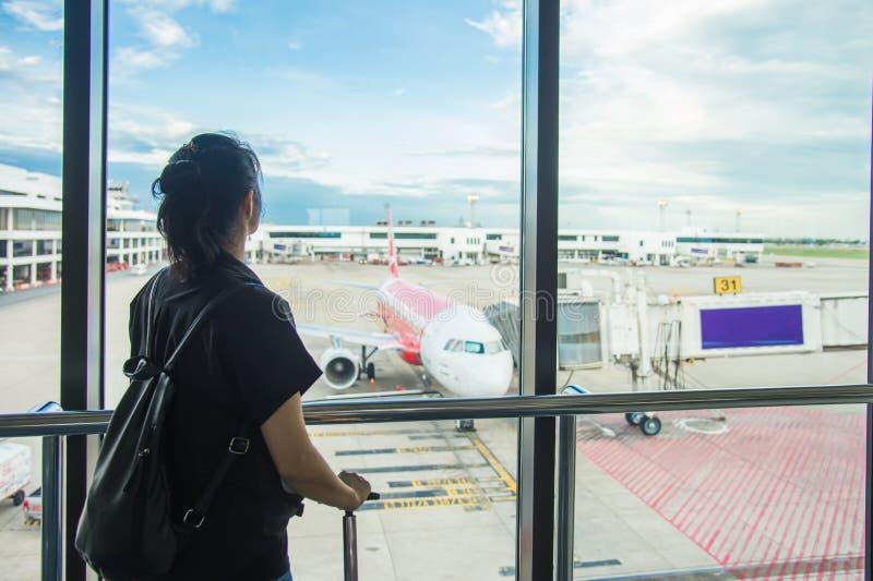 Vrouw die op een vlucht bij de luchthaven wachten; vensterluchthaven Jonge vrouw in de luchthaven, die door het venster vliegtuig royalty-vrije stock foto