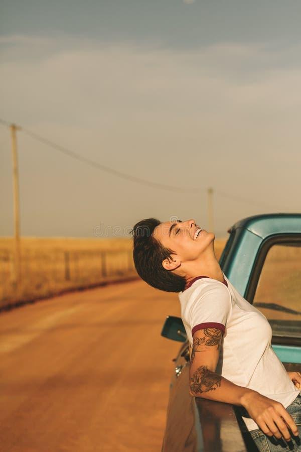 Vrouw die op een wegreis genieten van in haar auto stock foto