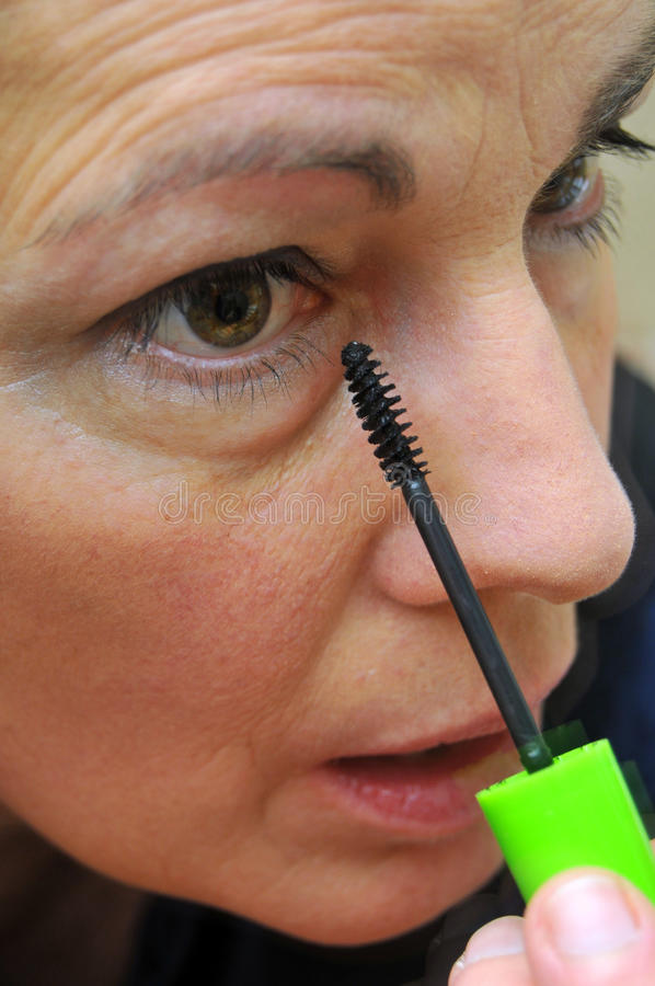 Vrouw die op eyeliner zet stock afbeeldingen