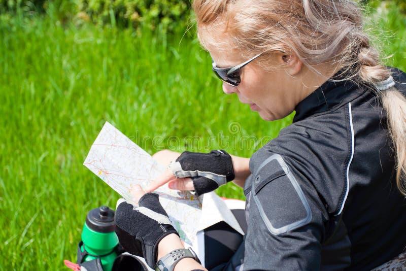 Vrouw die op fietsreis een kaart controleert stock foto's