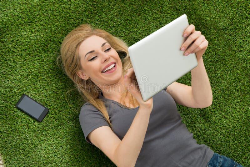 Vrouw die op Gras liggen die Digitale Tablet gebruiken stock fotografie