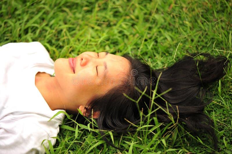 Vrouw die op gras rust stock fotografie