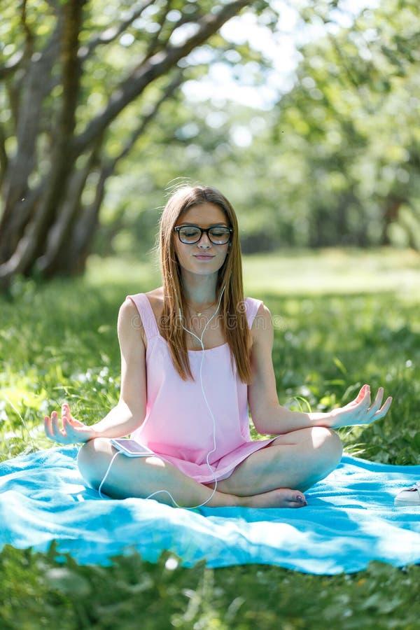 Vrouw die op groen gras bij de parkzitting mediteren in lotusbloempositie Geschiktheidsmeisje het ontspannen in yoga stelt na oef royalty-vrije stock foto