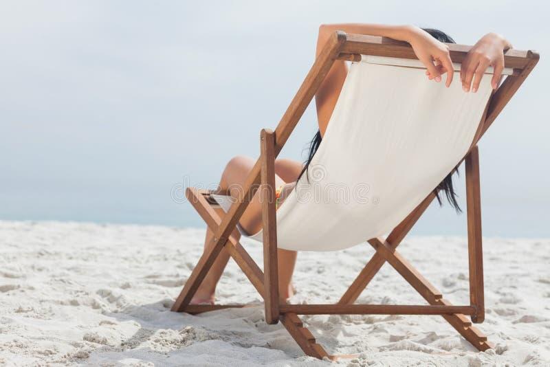 Vrouw die op haar ligstoel liggen stock foto