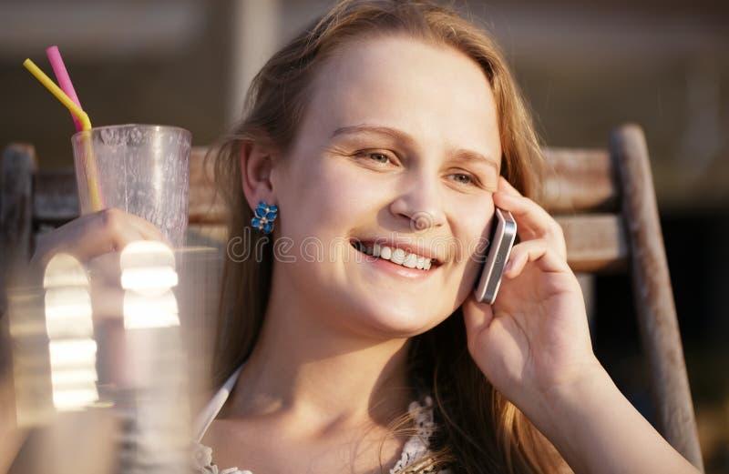Vrouw die op haar mobiele het drinken cocktail spreken en royalty-vrije stock fotografie