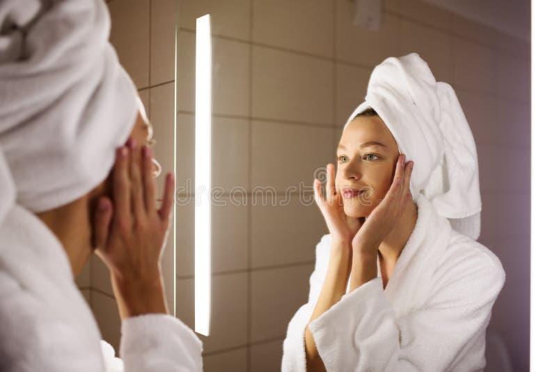 Vrouw die op haar spiegel kijken stock foto's